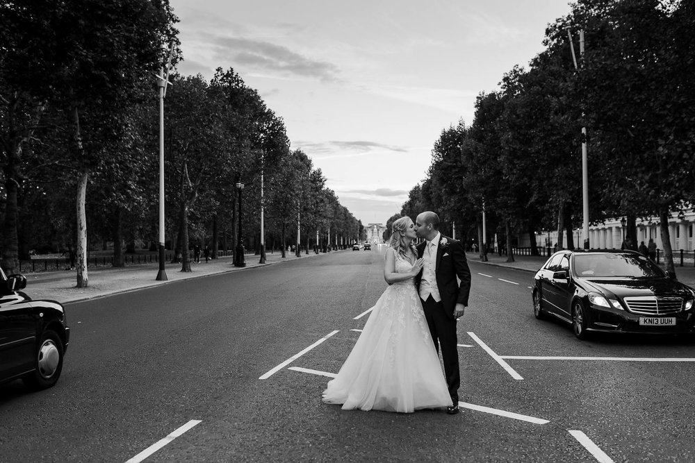 bride and groom in front go buckingham palace - Elegant London Wedding at the Royal Automobile Club