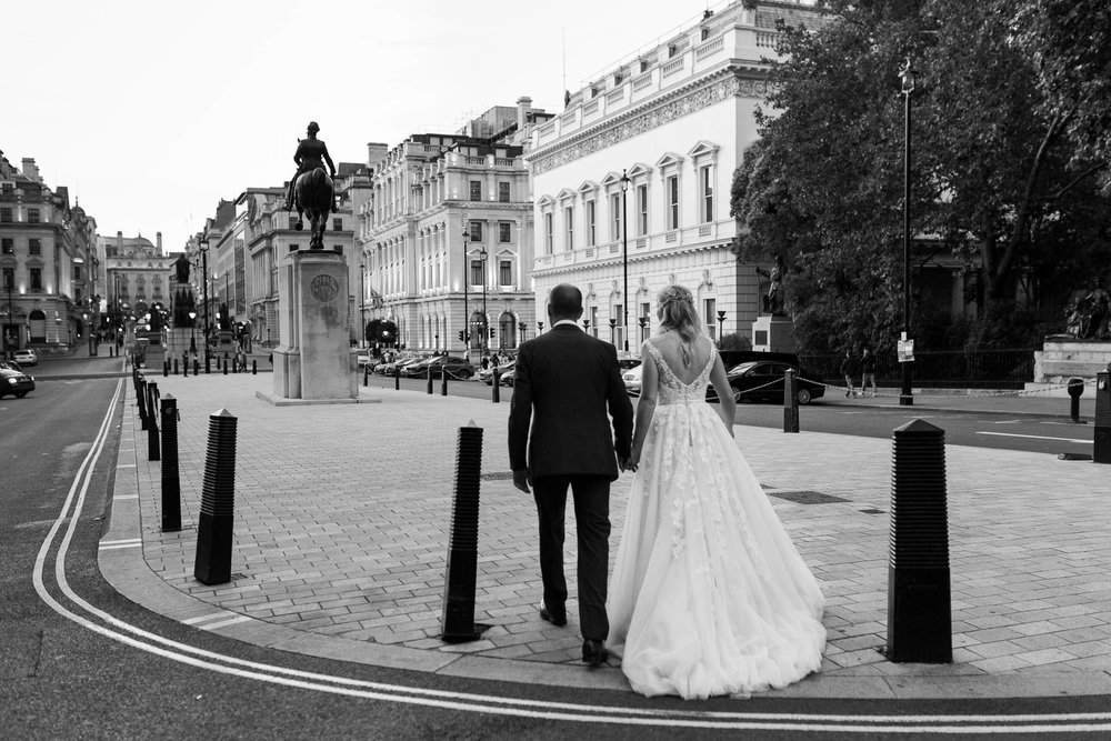 bride and groom walking through Pall Mall