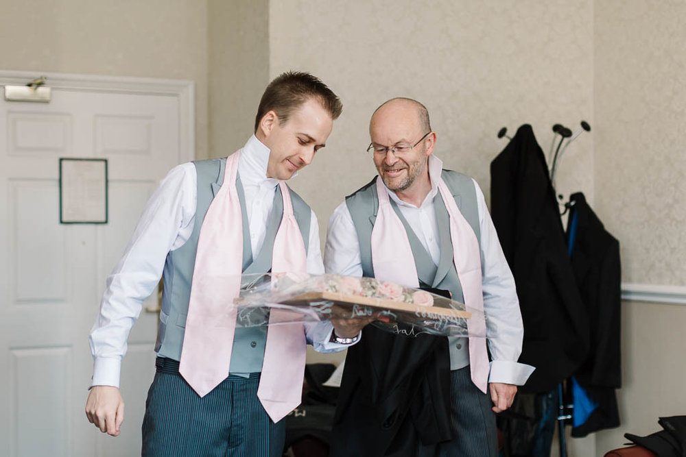 groom and father admiring button holes