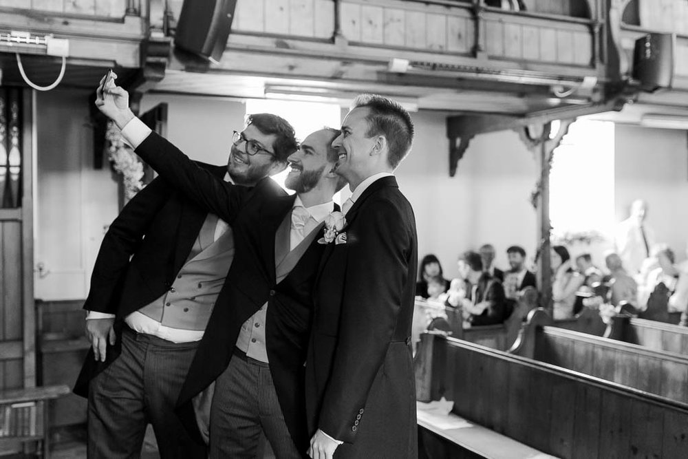 groom having selfie with groomsmen in church