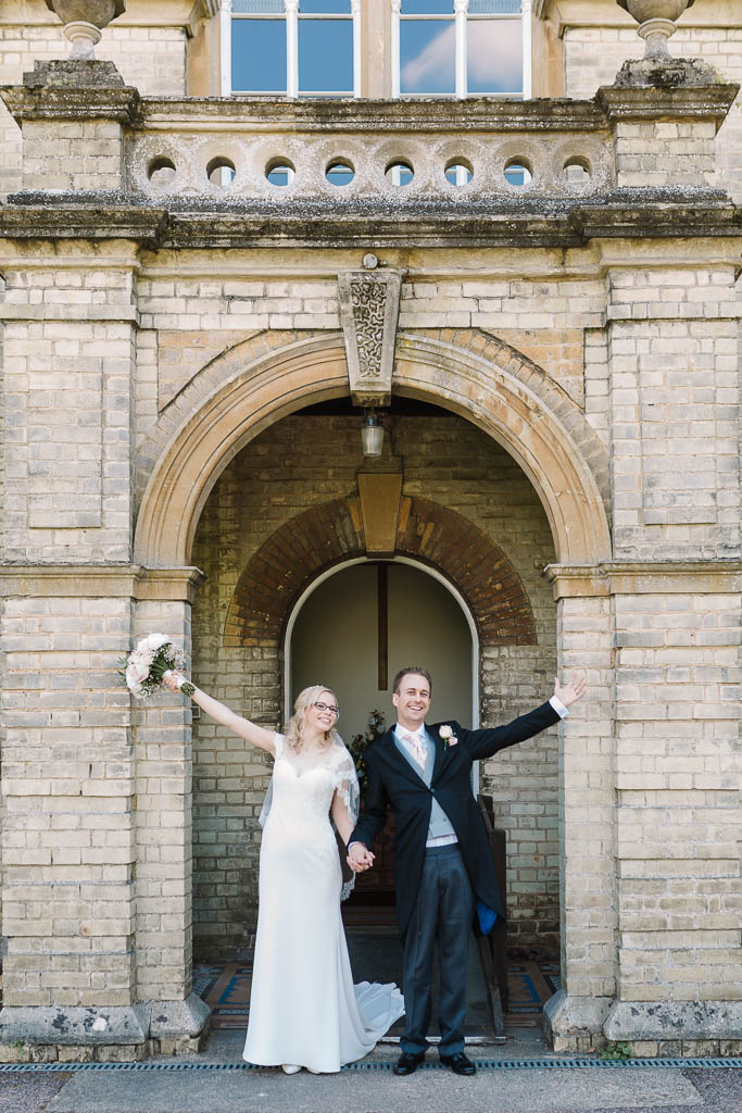 bride and groom cheering as they leave church - Fun Country House Wedding