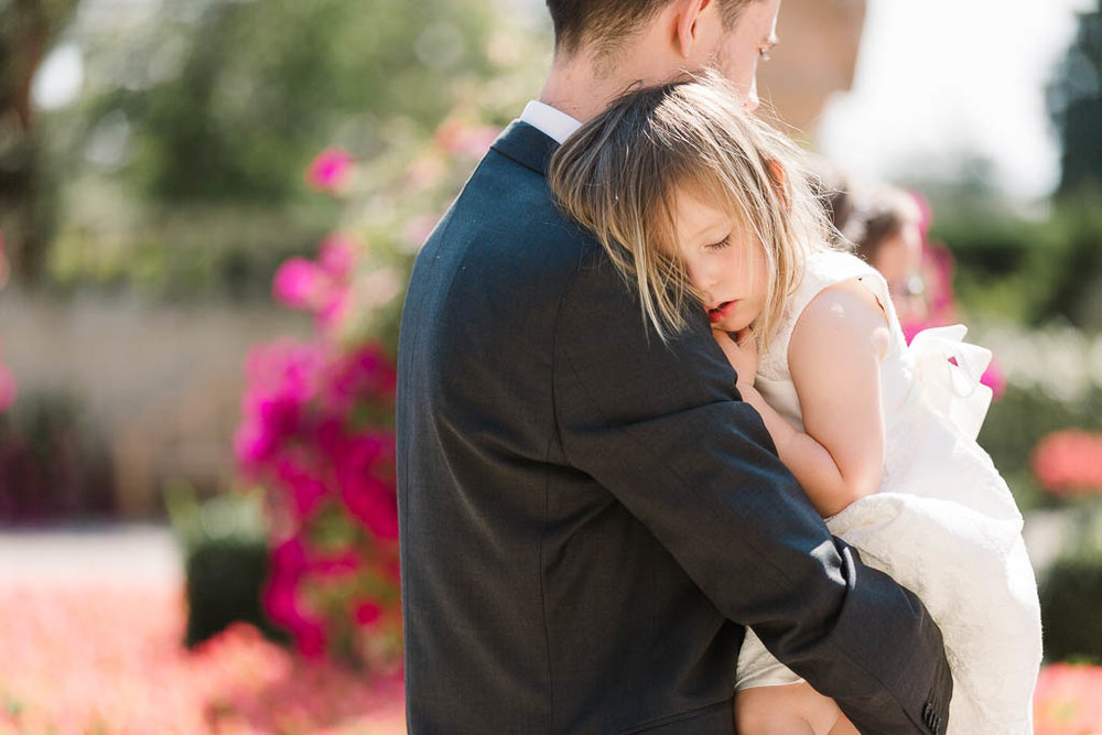flower girl asleep on dads shoulder