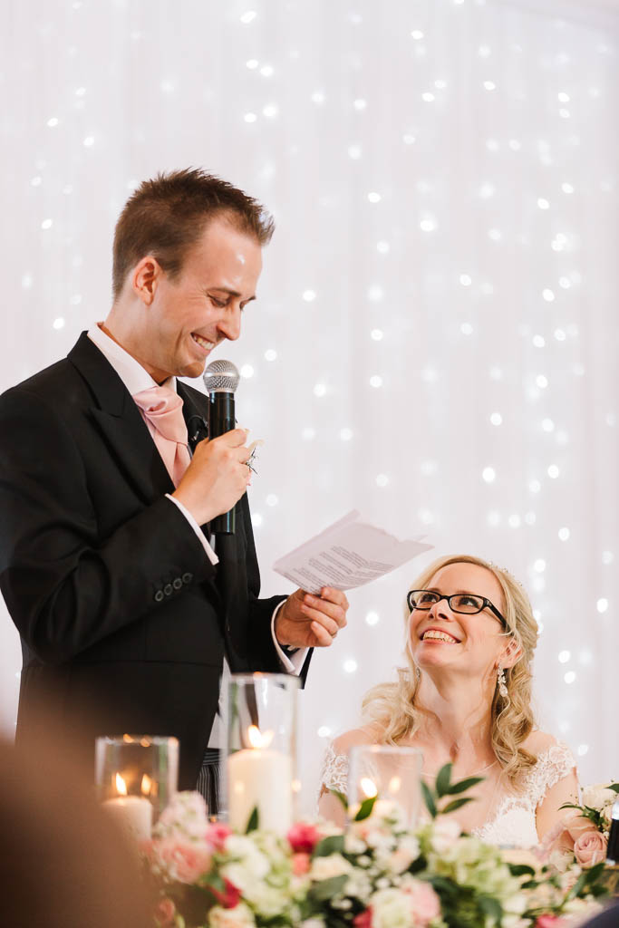 groom giving speech and bride smiling