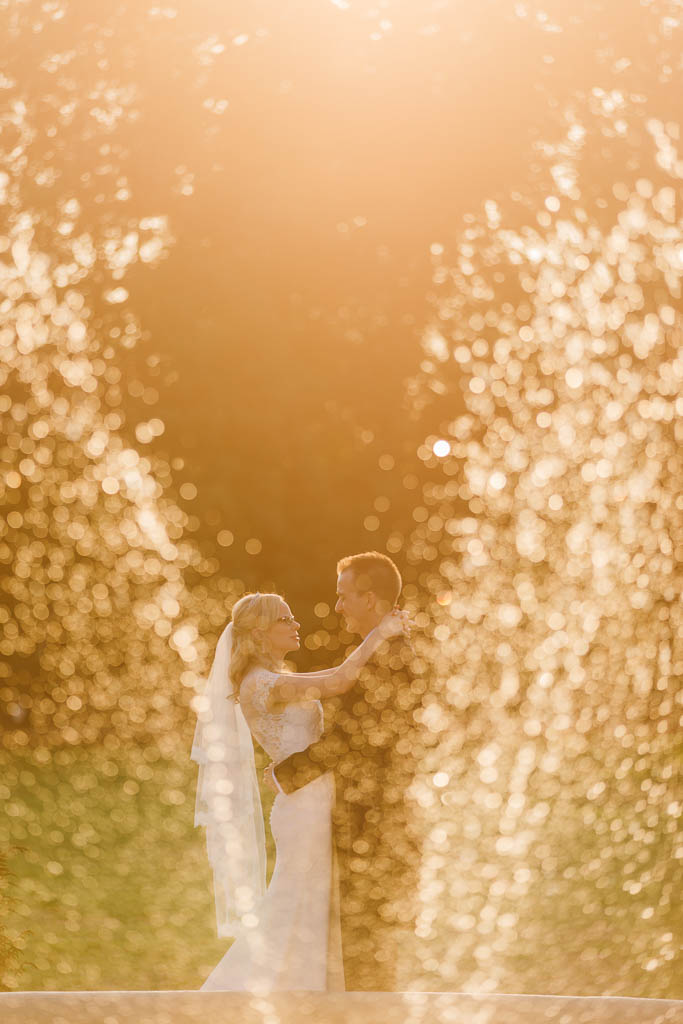 bride and groom behind water fountain at sunset