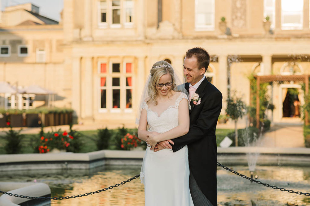 bride and groom smiling in front of country house