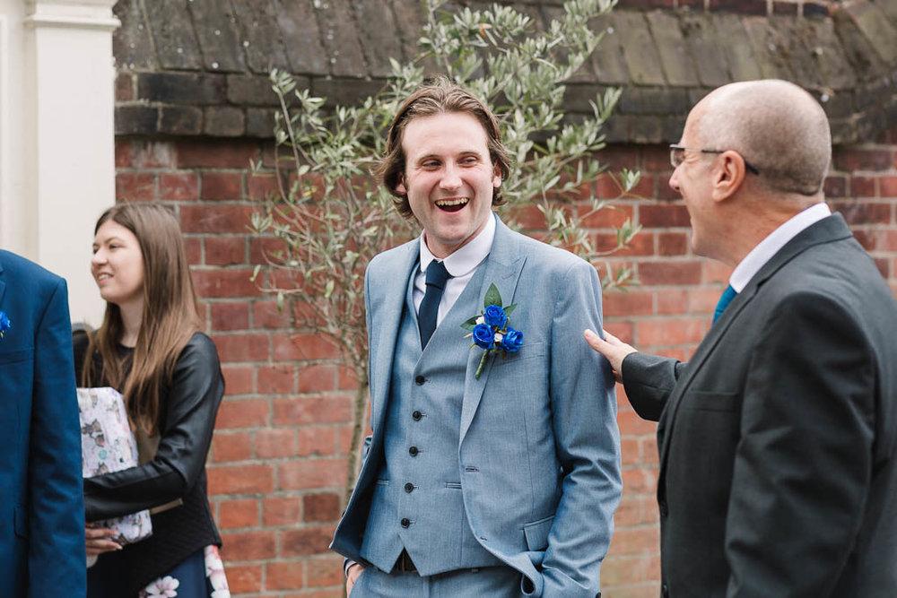 groom laughing - LANGTONS HOUSE WEDDING