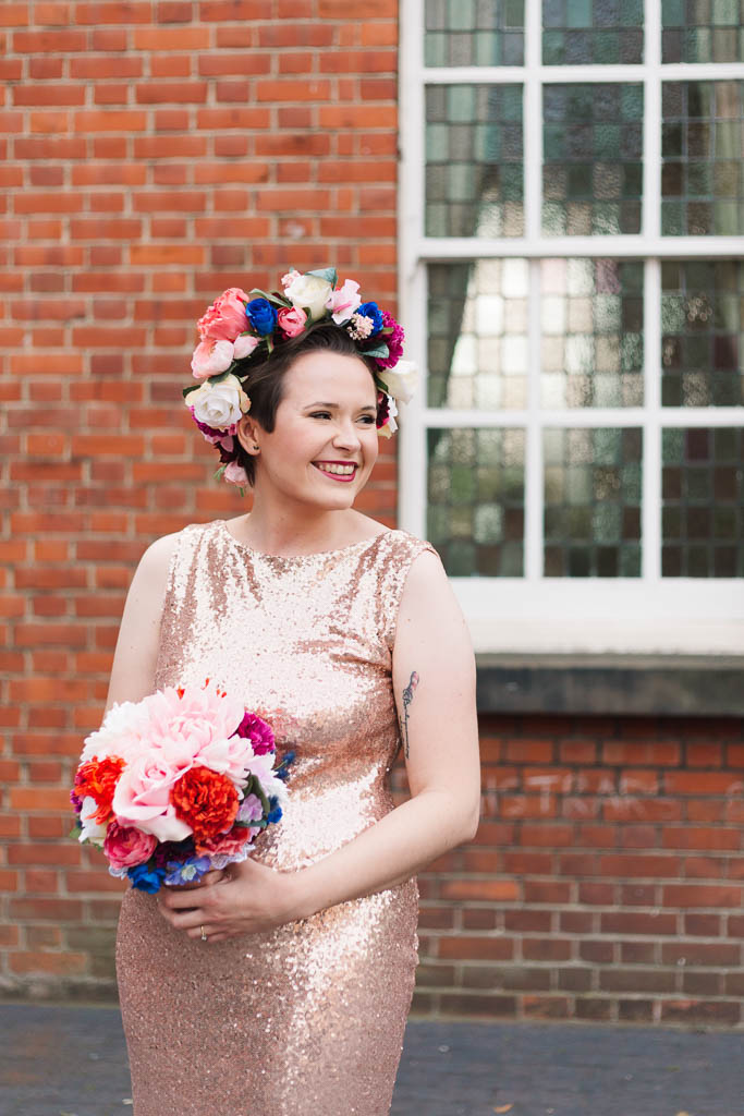 bride in gold sequin dress and colourful flower crown