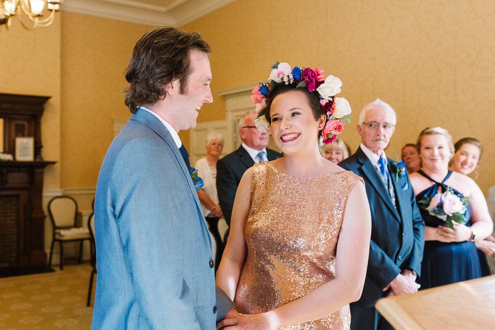 bride getting married in gold sequin dress and colourful flower crown