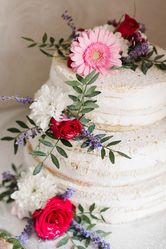 semi-naked wedding cake with colourful flowers