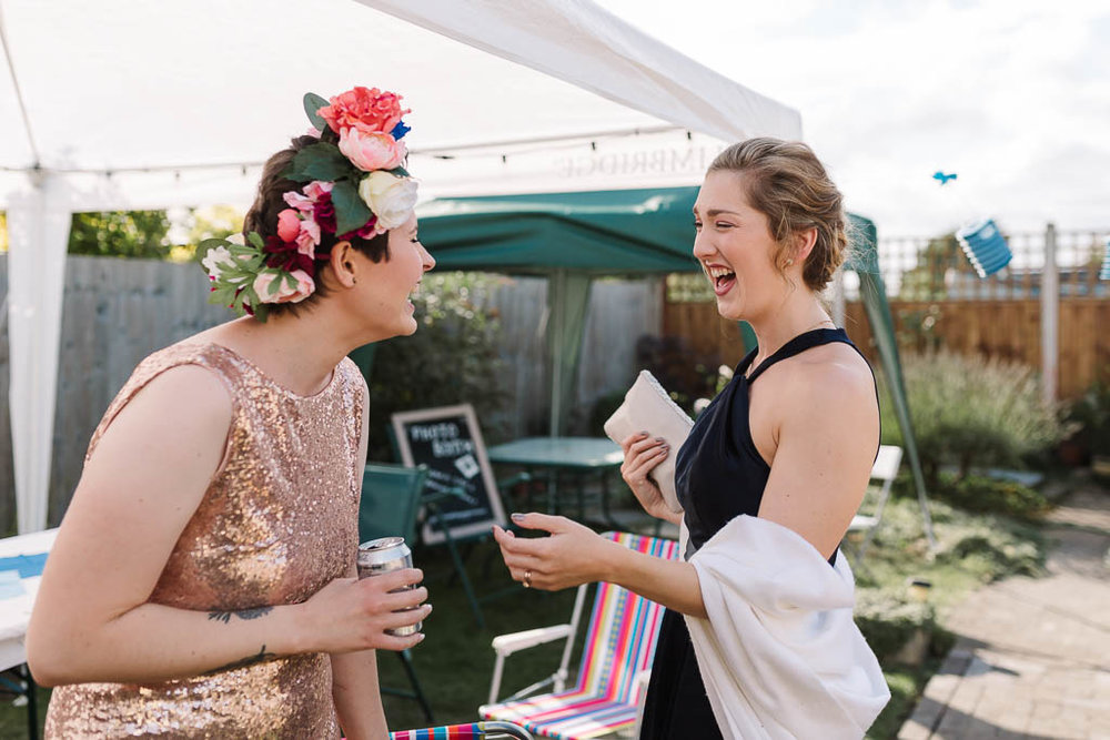 ride and bridesmaid laughing - LANGTONS HOUSE WEDDING AND CHILLED GARDEN RECEPTION AT HOME