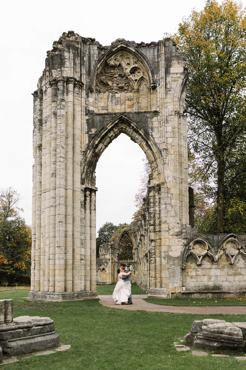 bride and groom hugging by the ruins at hospitium york