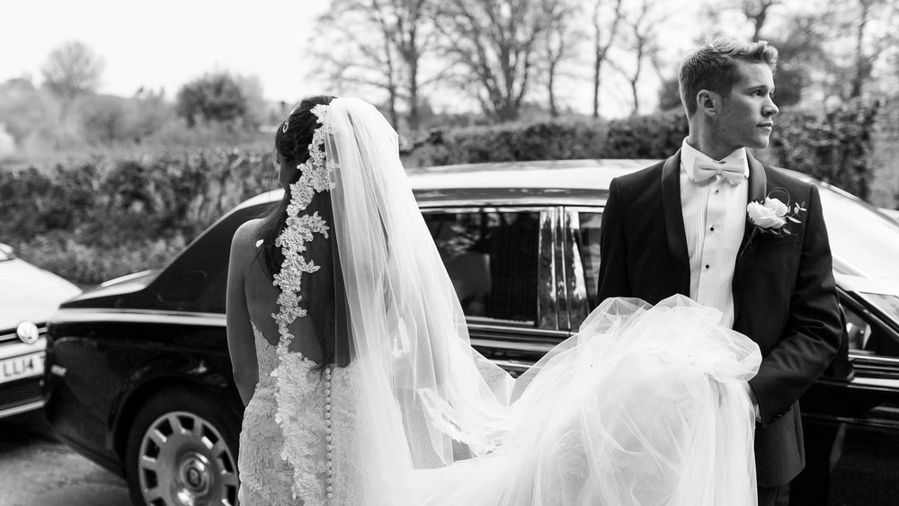 bride and groom waiting by car - essex wedding photography