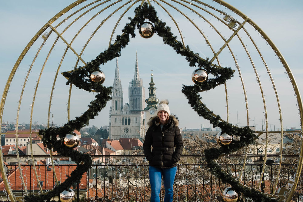 standing by christmas tree with view over city
