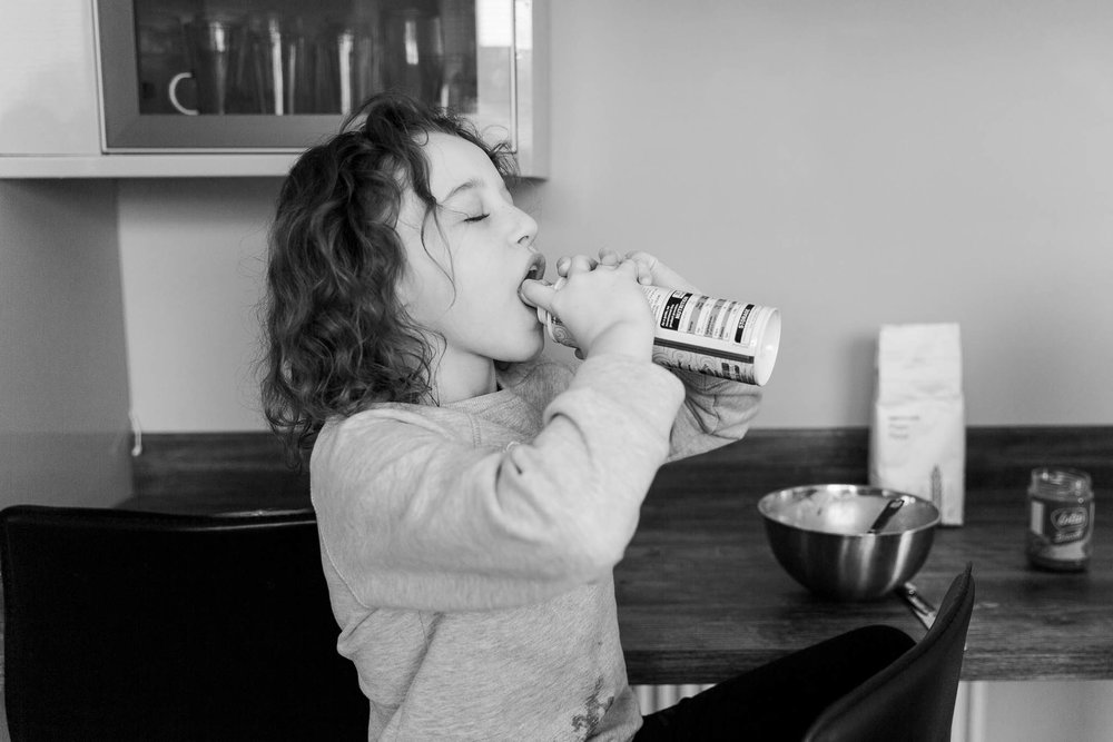 little girl squirting cream into her mouth