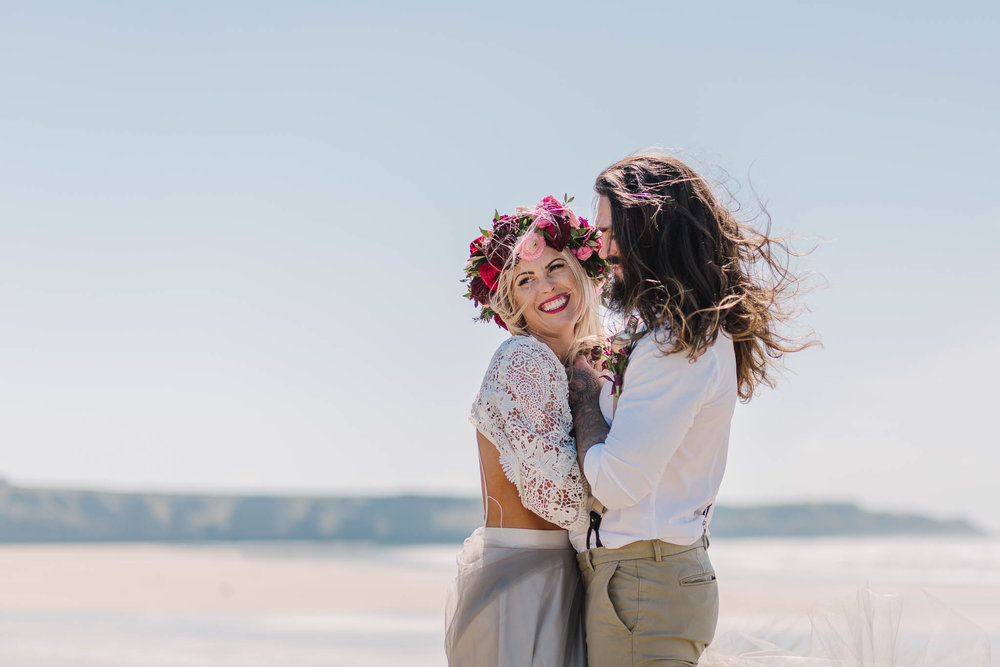 bride and groom laughing at beach wedding