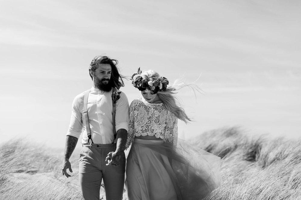 bride and groom walking through sand dunes
