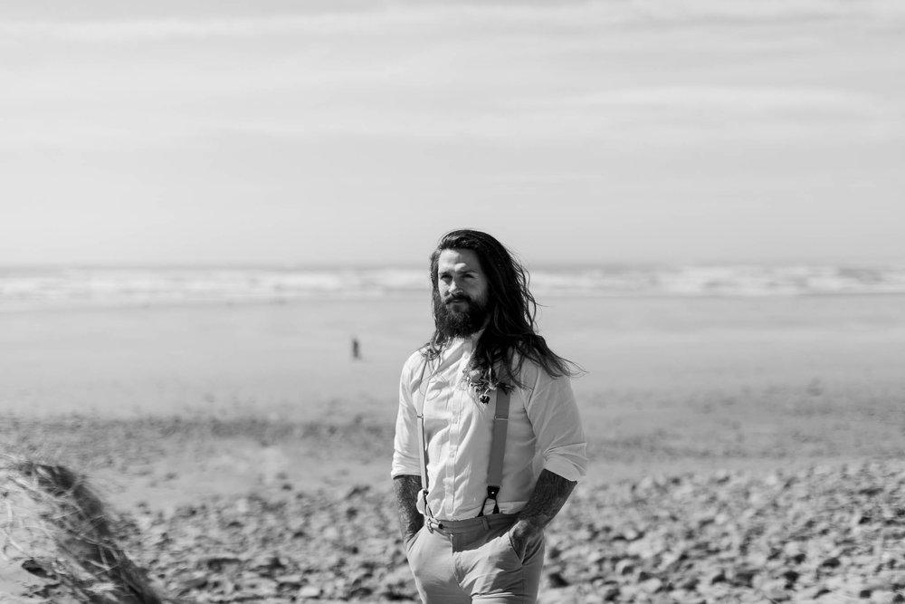 groom standing on the beach