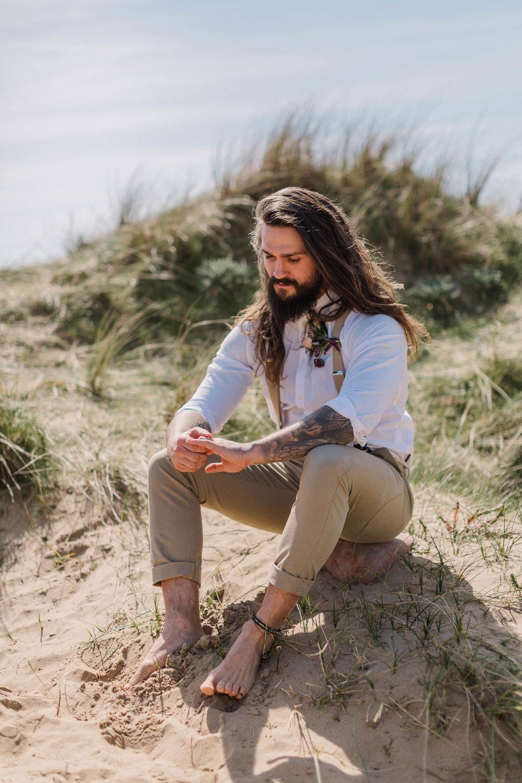 groom sitting on sand dunes