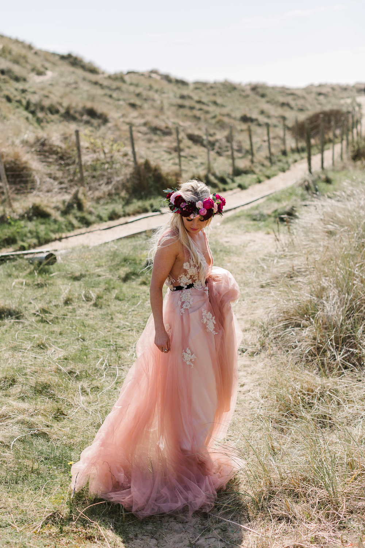boho bride wearing pink wedding dress and flower crown
