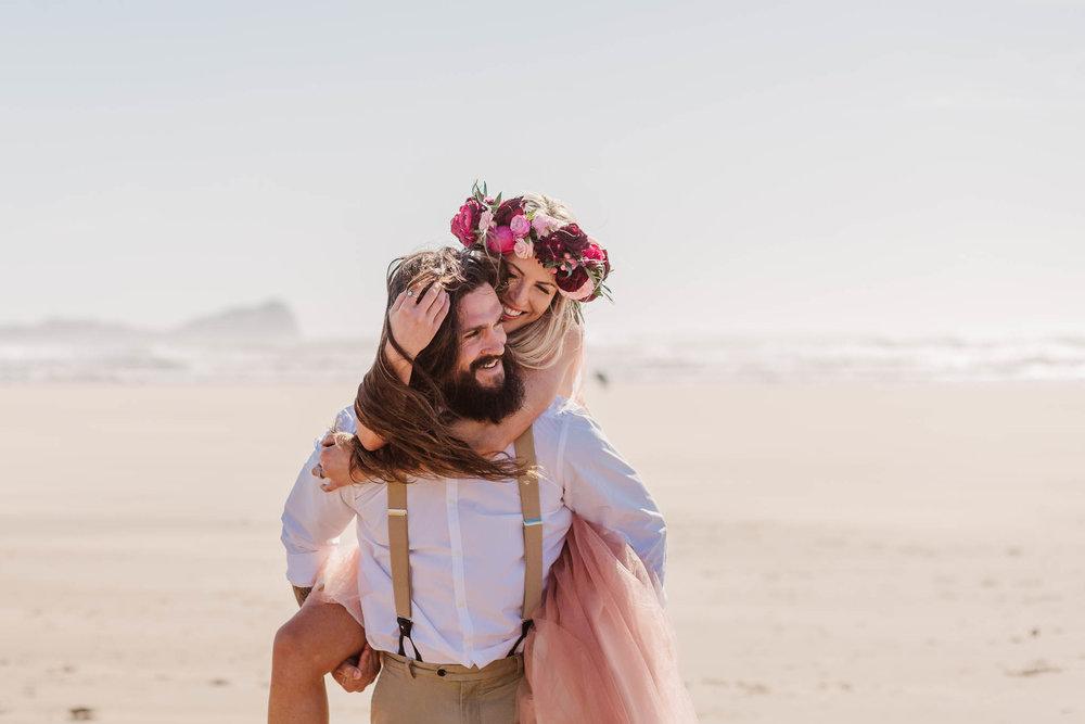 groom giving bride piggy back on beach