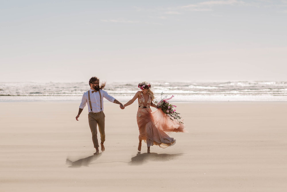 bride and groom running on the beach together