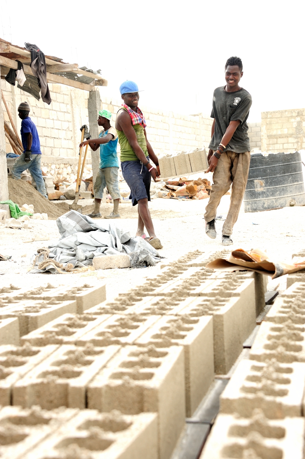 two of claude debrosse's employees carry newly poured cinderblocks to the drying area.  photo: fonkoze USA/kiefel photography