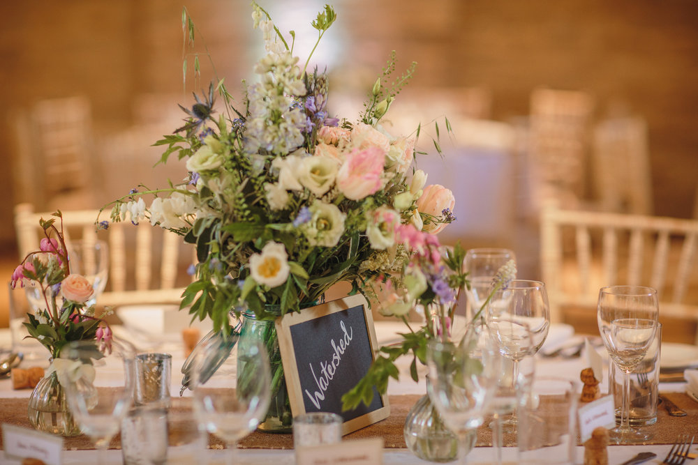 April. when the English sweet peas are grown under glass and we get  some summer scent in earlier than expected, when the tulips are at their best and when all that glitters is actually gold sequins. I do love a bit of magic and sparkle and we combined a loose pastel combination of spring florals with gold sparkly runners for this beautiful wedding at Tithe Barn near Petersfield the flowers were in pretty pale blue Kilner jars.