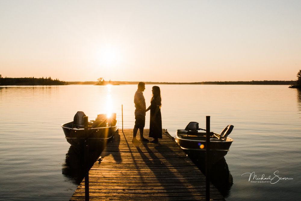 Couple on a dock with sunset in background