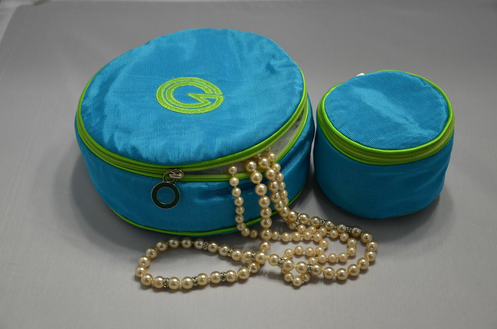 "1 and 6. Large and Small Round Jewel. Shown in Grotto Benglaine Moiré with Lime Satin Trim.  Large round jewel is 6"" in diameter, Small round jewel is 3"" in diameter.  Interior is velvet lined with multiple pockets for smaller valuables.MSRP Small rd Jewel $60, Large rd jewel $80"