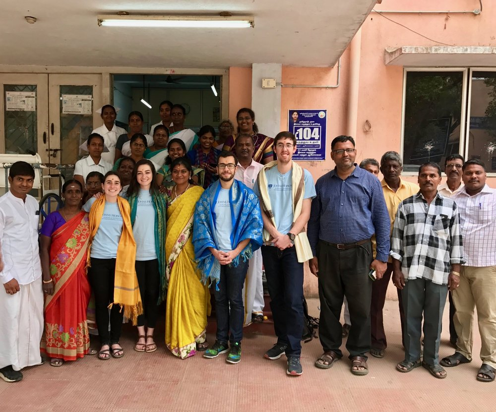 The Chennai, India IDEV Practicum Team gathers with doctors, nurses, and staff outside the Poonamallee urban primary health center (PHC) following interviews and observations. The PHC staff presented colorful scarves to the team as they were welcomed to the center.