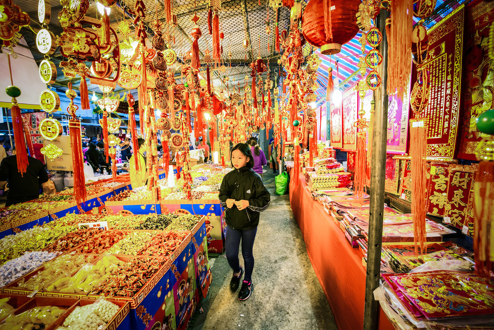 A young Taiwanese girl browsing a candy vendor's stall