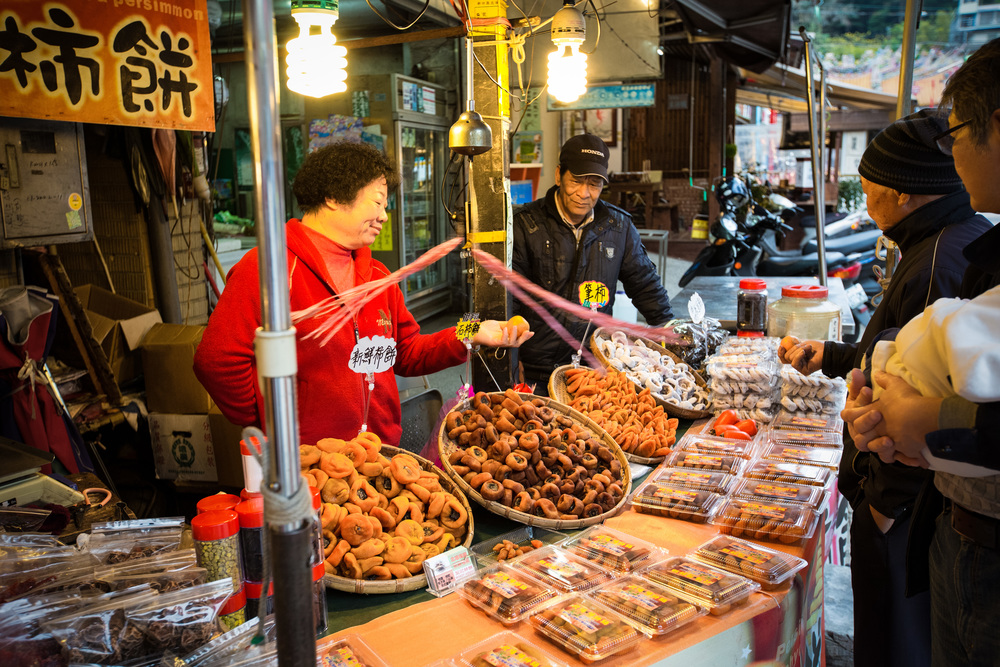 A vendor showing off her dried persimmons (柿餅), a specialty in the area.