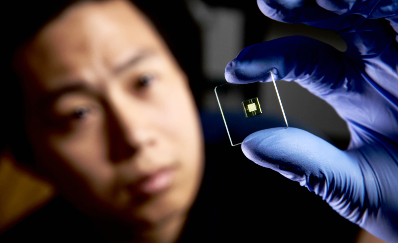 Image of PhD student Hua Gong looks at a 3D-printed microfluidic device.
