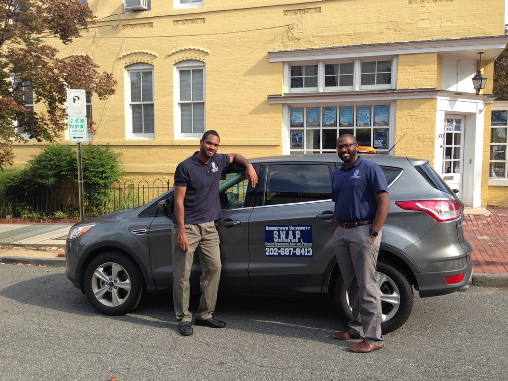 Theon O'Connor (burleith community director) and PT Jones (Assistant Director) of GU's Office of Neighborhood Life pose outside their office at 1300 36th Street NW. Photo courtesy of Office of Neighborhood life.