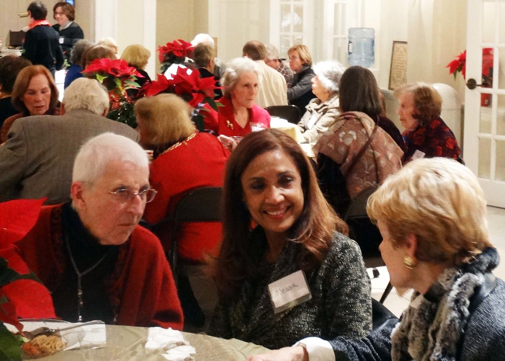 members and volunteers mingle over dinner.