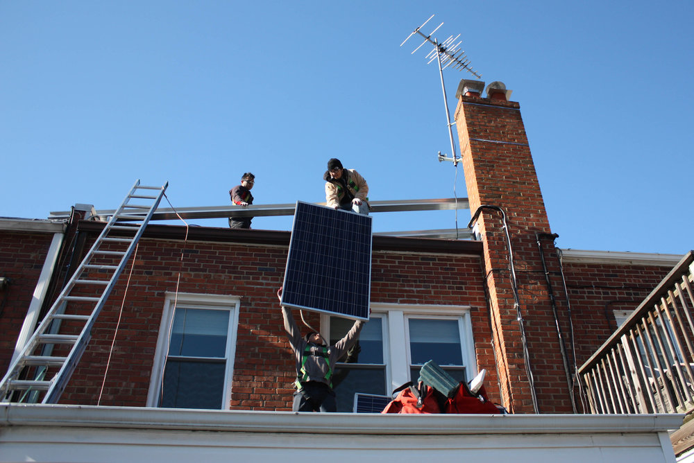 A crew installs solar panels on a Burleith home last winter.
