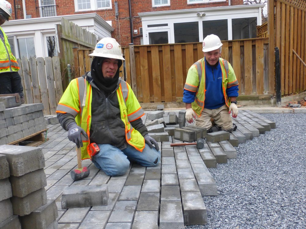 After the permeable paving is laid, smaller gravel is swept in between the spaces.