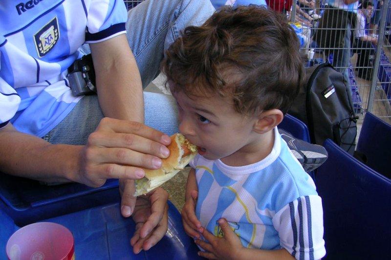 Mateo recibe de su responsable padre una nutritiva porción de comida típica del lugar