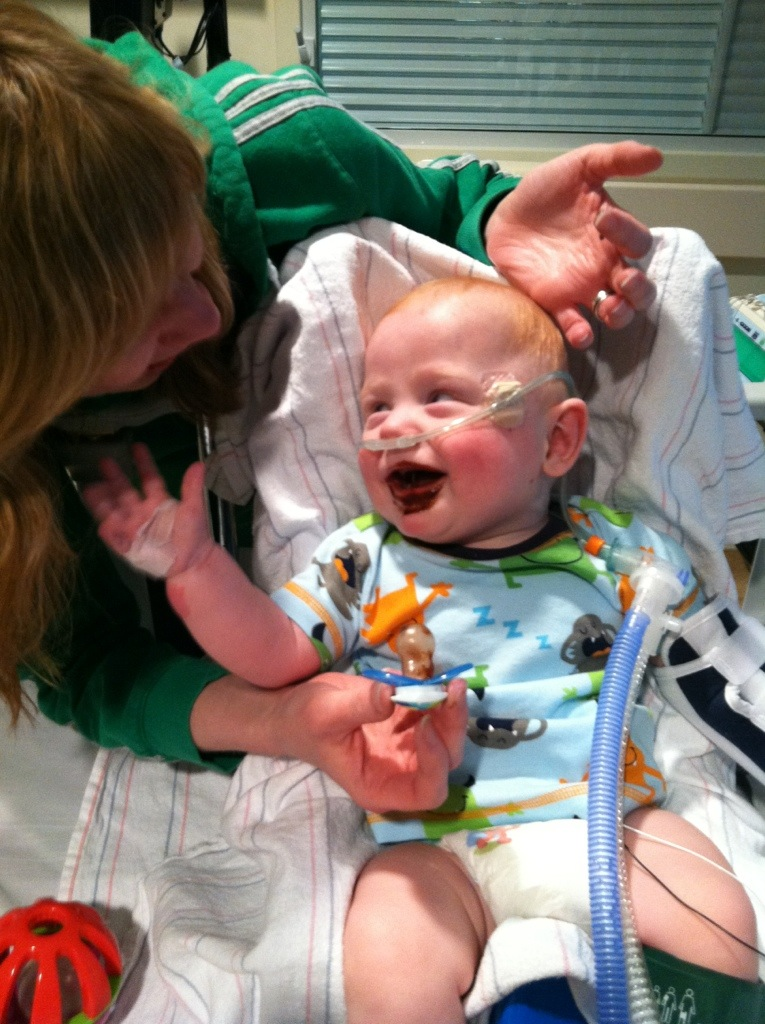 smiling preemie in the NICU with oxygen