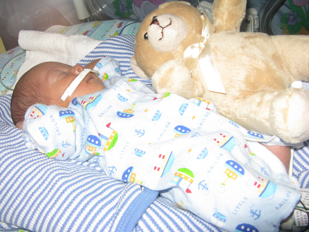 NICU preemie with teddy bear, NG tube