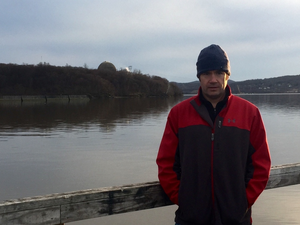 Christopher Swain stands beside the Hudson River in Peekskill, New York in March 2016. The Indian Point Energy Center nuclear power facility is partially visible on the hill behind him. (This image belongs to Christopher Swain.  Members of the news media: you are welcome to use this image.)