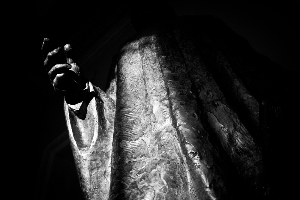 "Afternoon light falls on a bronze statue near the Senate chamber in the Capitol. In the midst of the turmoil, the credit rating agency Fitch put the United States on a ""negative ratings watch,"" warning that Congressional intransigence had put the full faith and credit of the government at risk."