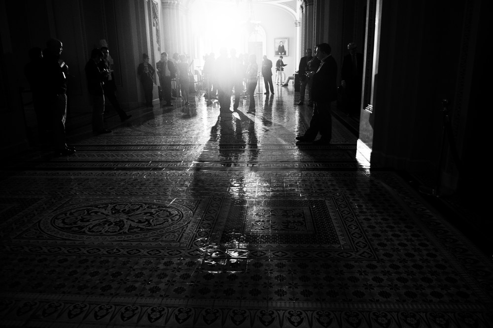 Camera lights shine through the halls as reporters wait to hear from other members of Congress about the deal.