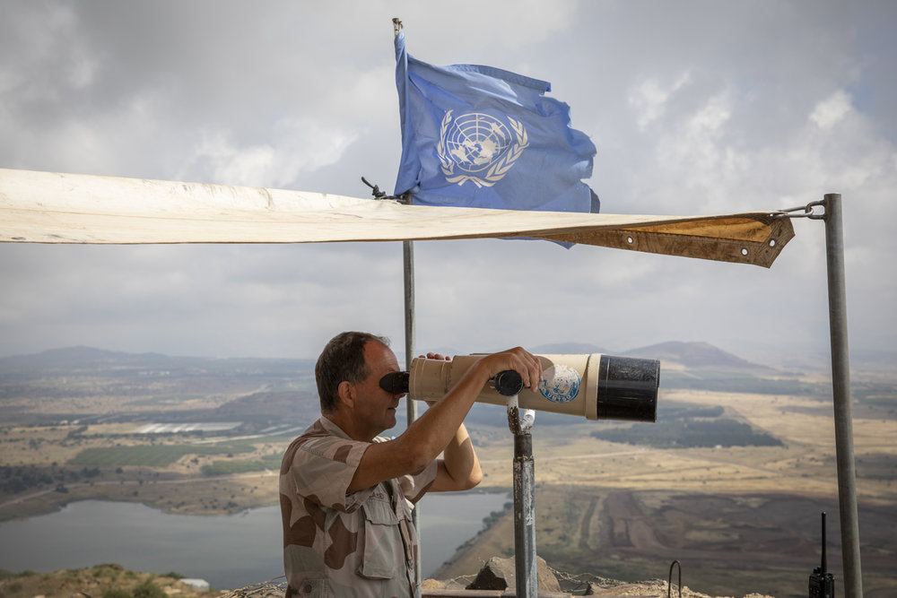 A UN peacekeeper keeps lookout on top of Mount Bental in the Golan Heights which overlooks the Syrian border less than a mile away.