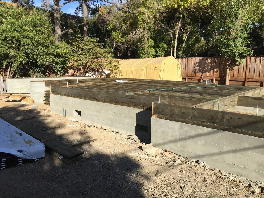 The wide open stem walls begin to fill up with floor joists and girders. Rim joists are added cap the ends at the edge of the mud sills.