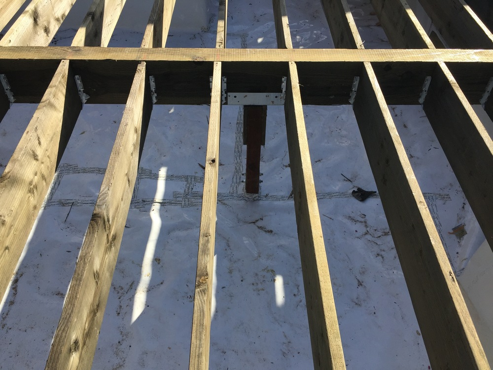 """Here is a post that supports a floor girder. You can see how they've taped up the membrane where it breaks and around the post itself too. It's all pressure treated lumber at this point, so moisture passing thru is actually """"o.k."""""""