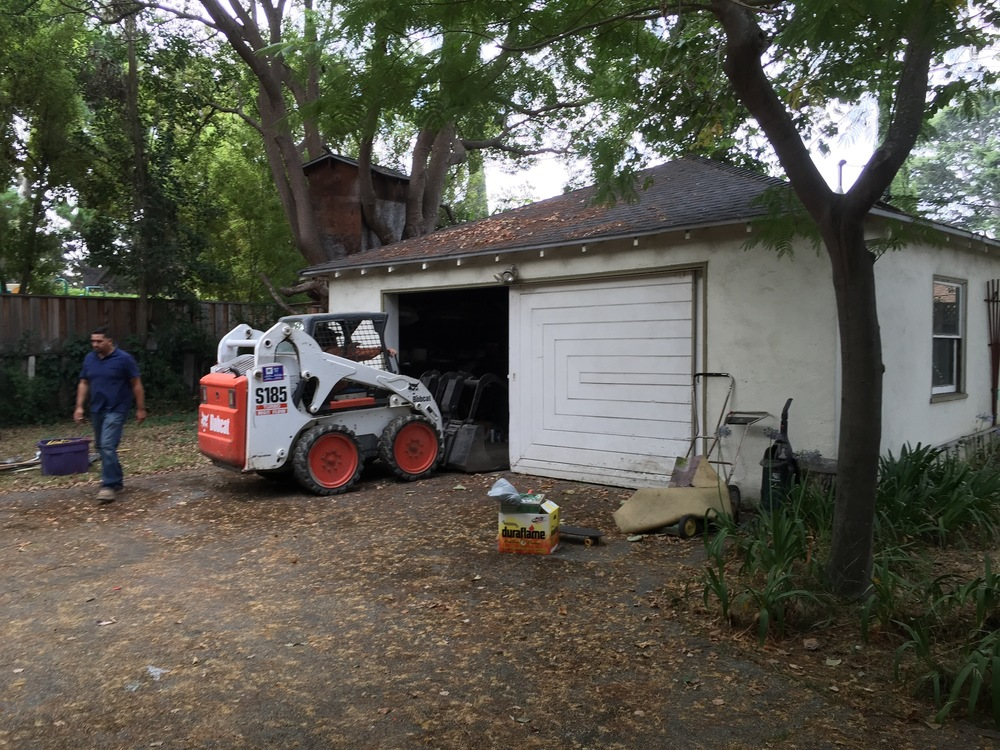 Here's the bobcat on demo day. The first thing to go? The sliding garage door.