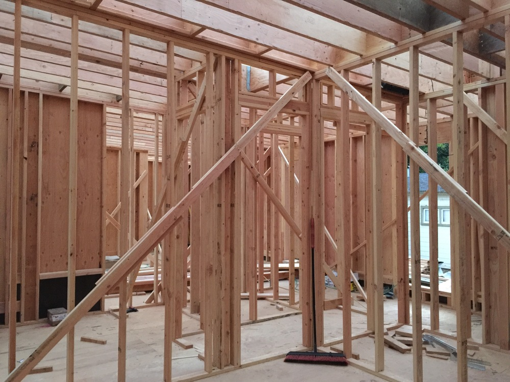 The rafters are now almost all the way across the house as you look up. The diagonal members are temporary kickers and braces until the plywood sheathing goes up for additional shear strength.