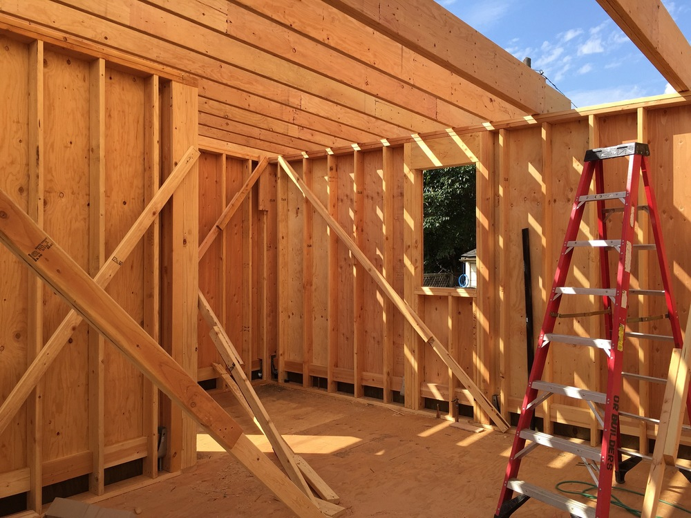 This is what the inside of the house looks like behind the plywood wall sheathing. You can see the ceiling/roof joists making their way down the house, in this view, from left to right.