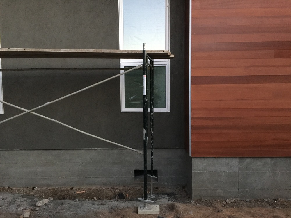 Here's a good picture that portrays all three. Dark gray is the stucco (brown coat), wood siding to the right, and concrete stem wall lining the bottom.